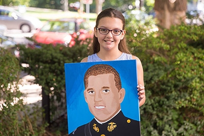 Amelia B with her painting of Travis Manion for the Portraits of Change Art Show